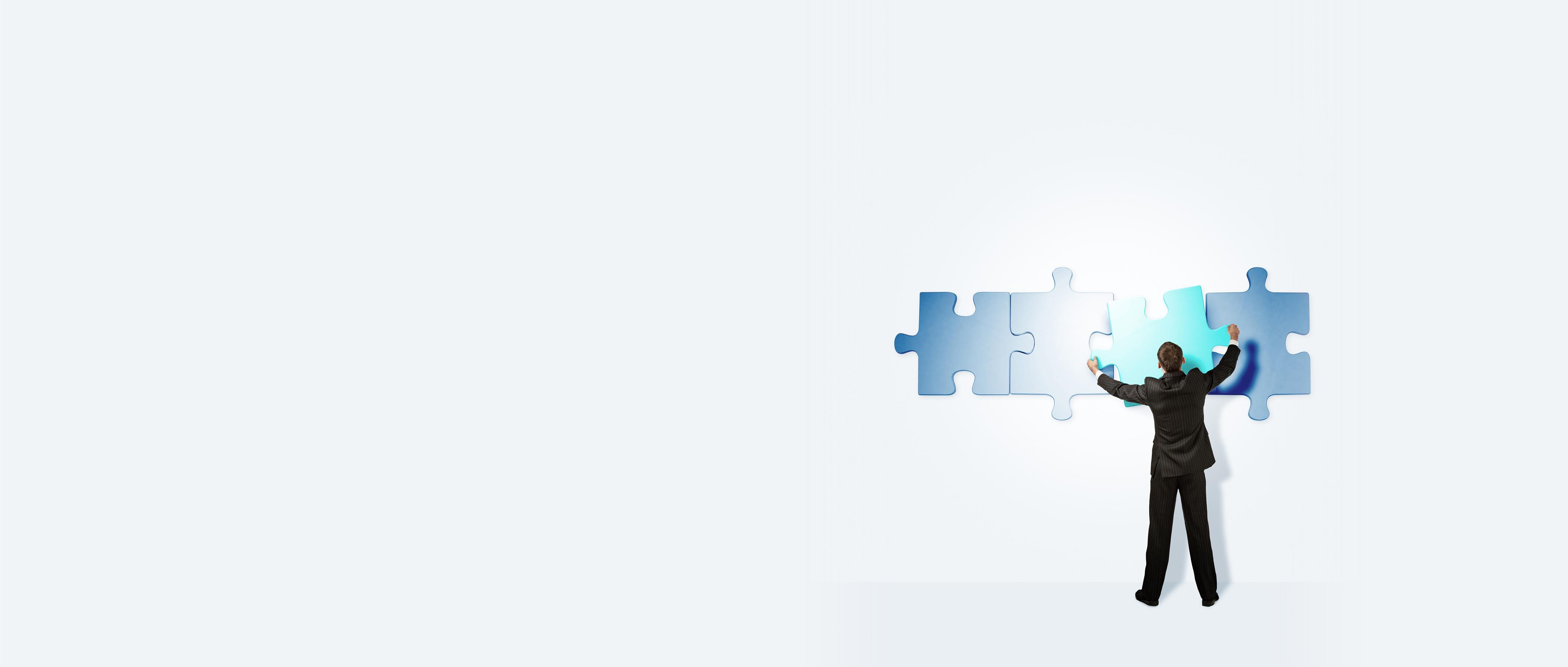 Man assembling puzzle pieces on white background