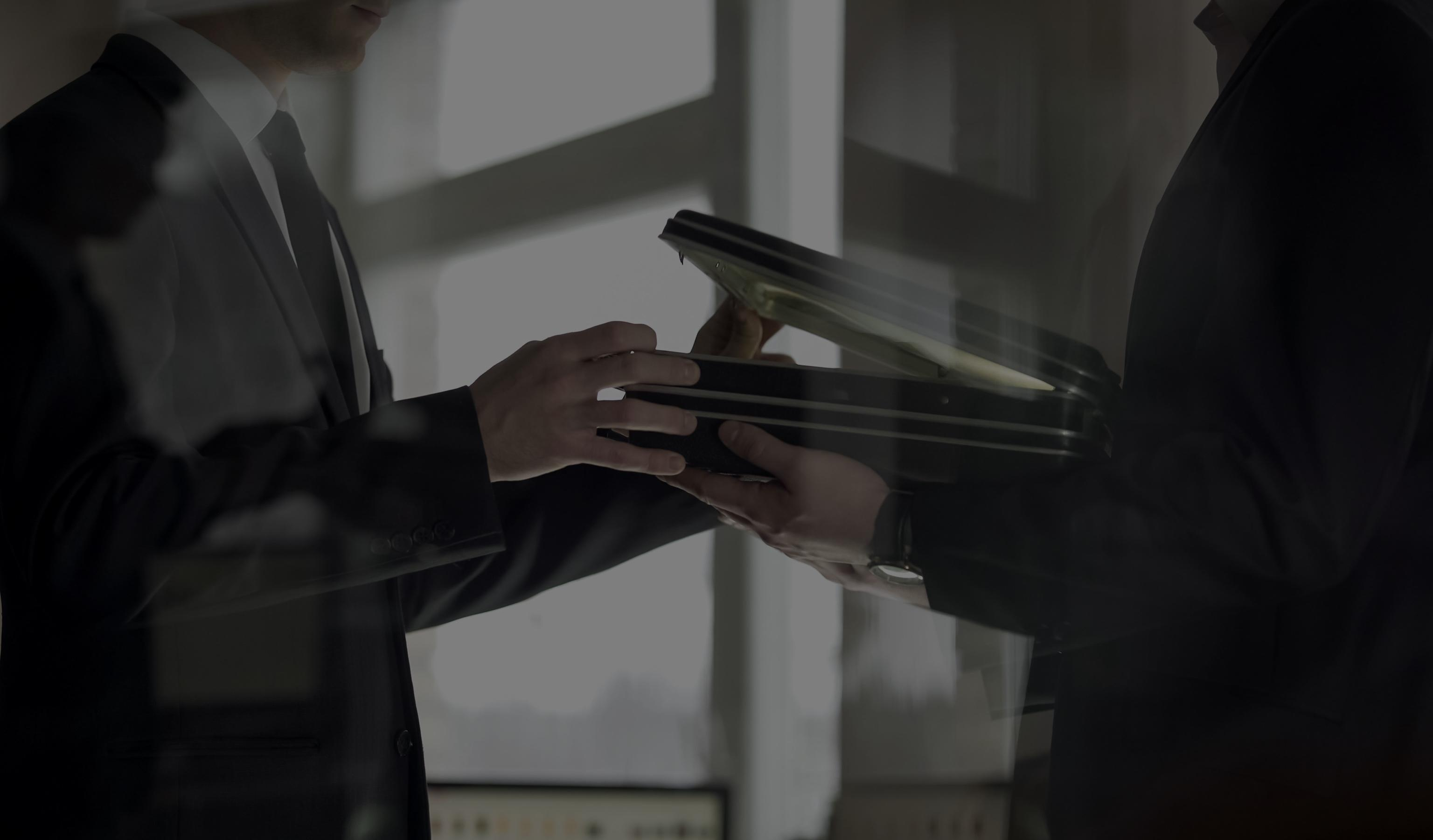 Businessman showing another businessman a suitcase full of confidential documents