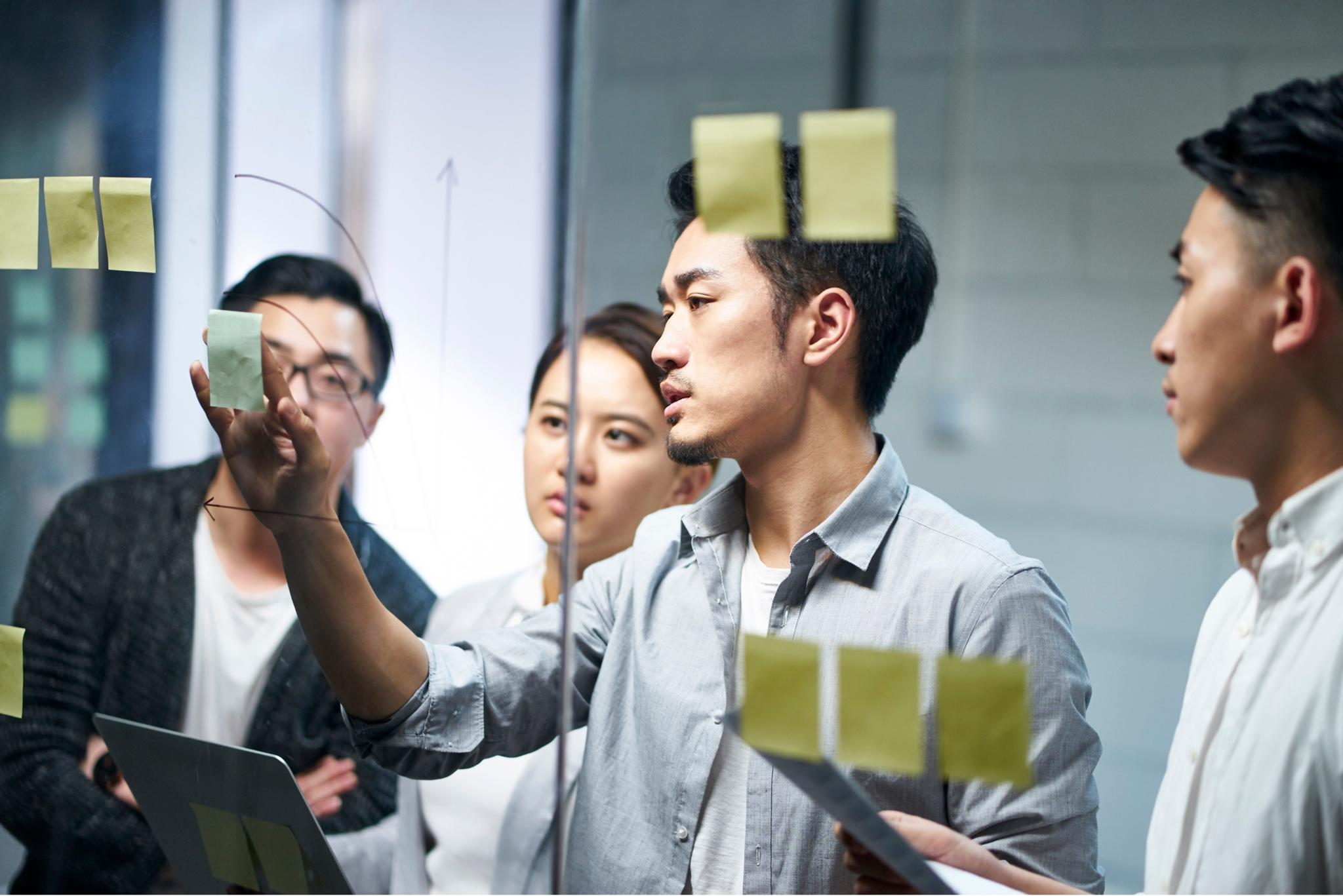 Businessman putting a adhesive note on glass in office during team meeting, formulating business strategies.
