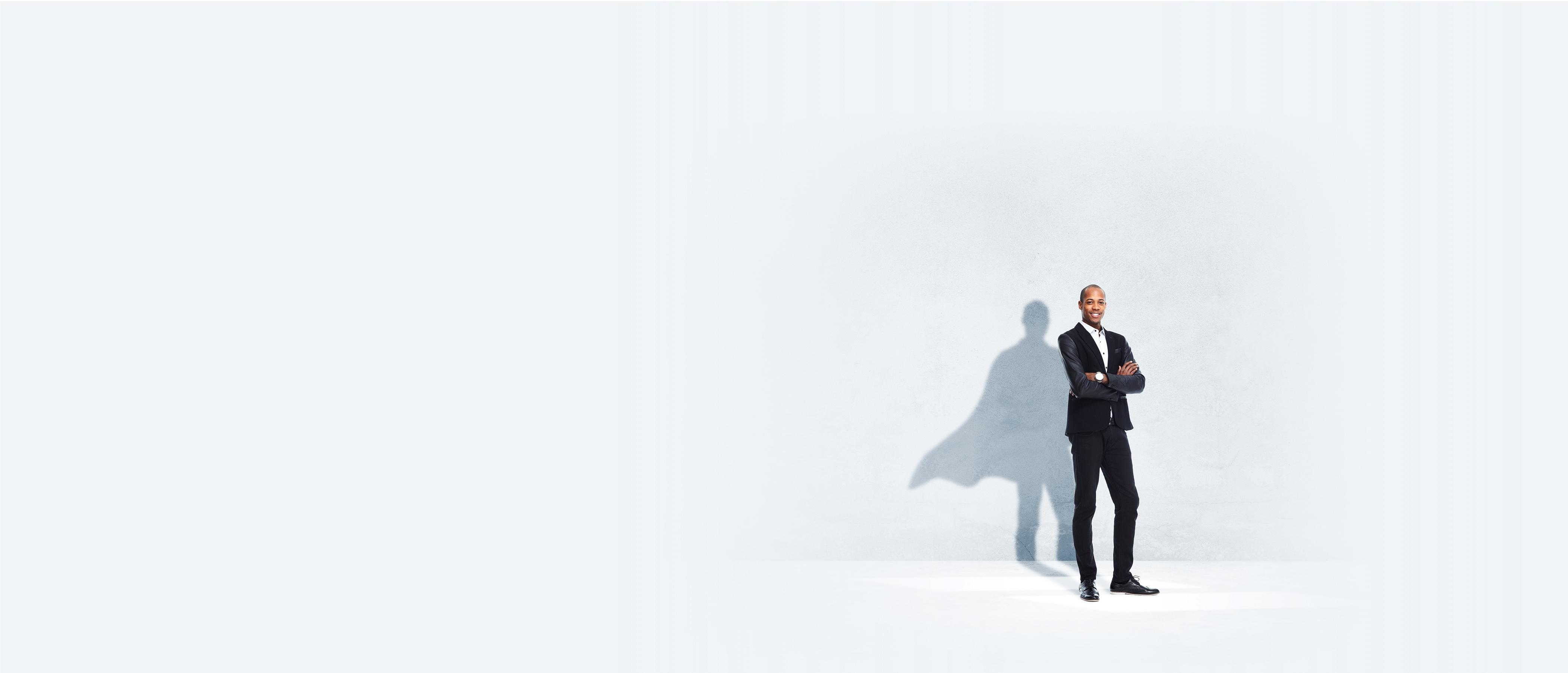 Businessman standing confidently with a caped-superhero shadow behind him