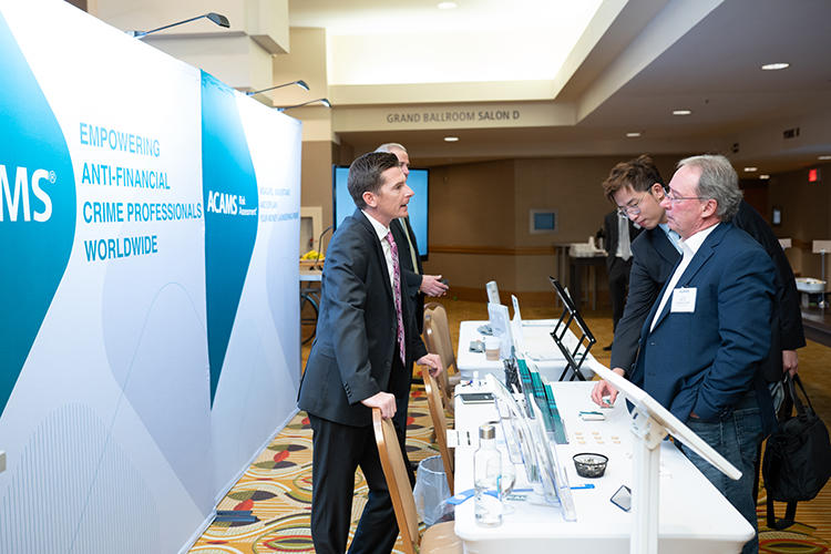 Business people talking at conference stand