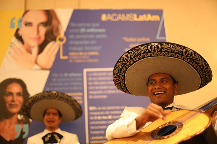 Mariachi guitarist smiling and playing guitar.
