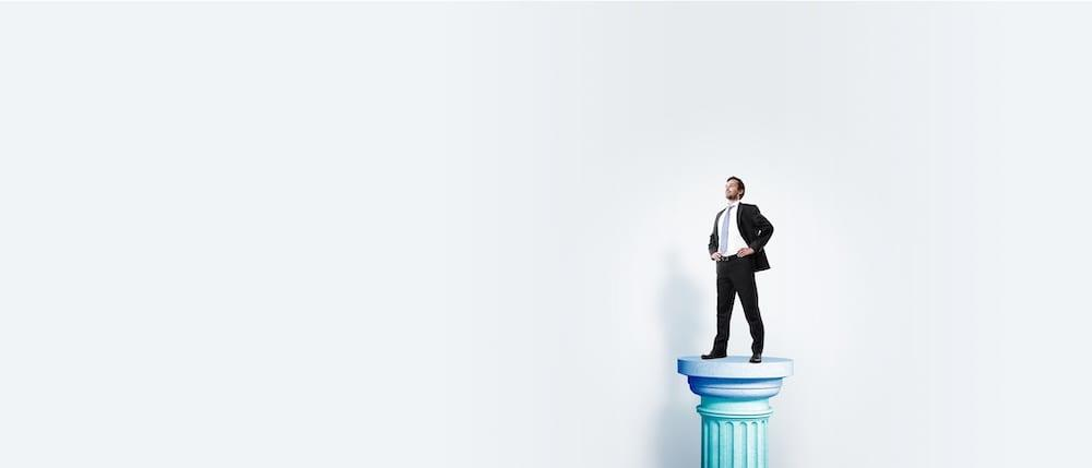 Business man standing proudly on a column