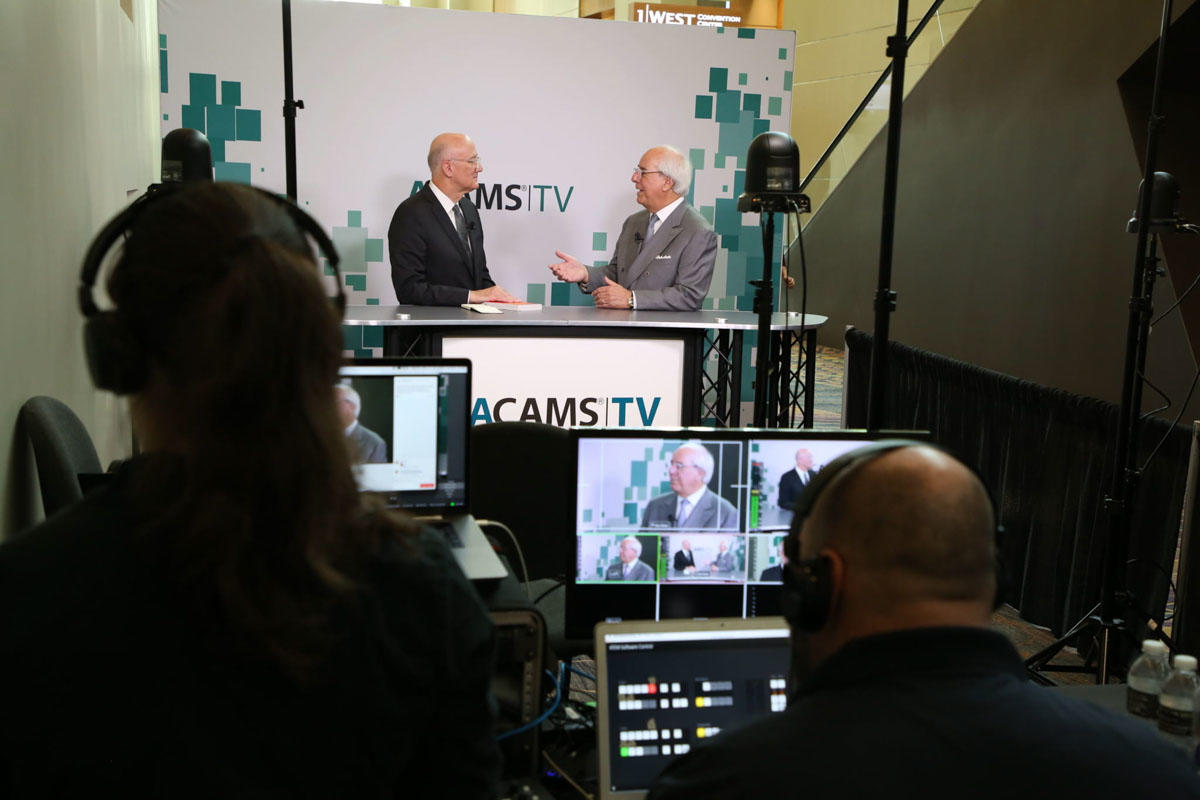 Two business men being broadcast speaking on ACAMS TV