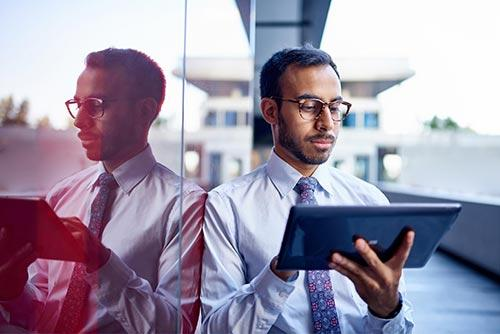 Businessman leaning on a dark glass wall while holding a tablet