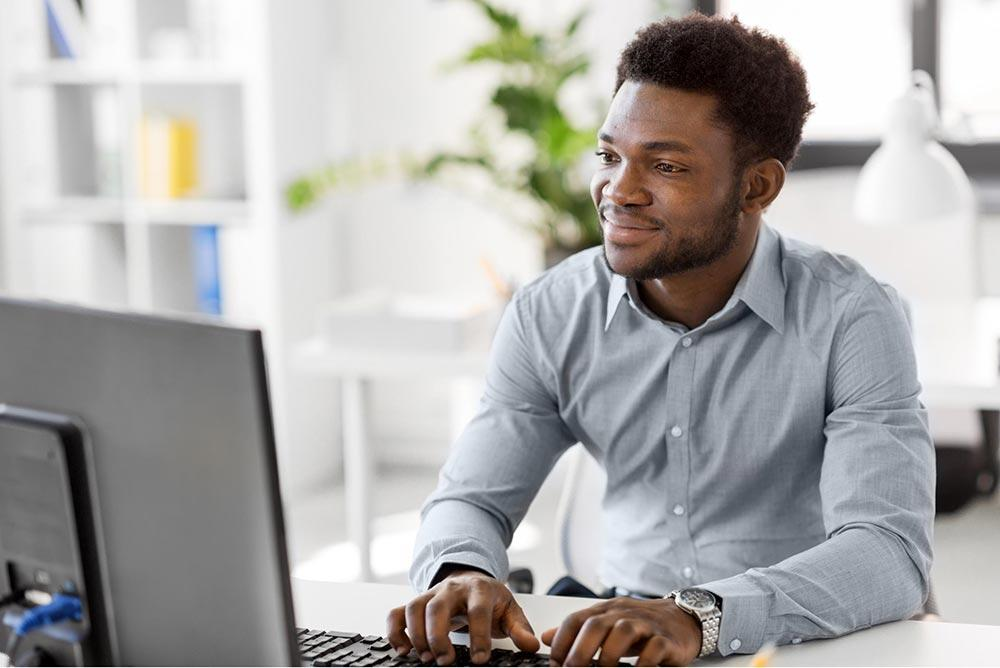 Confident man in business casual attire working on his laptop at home
