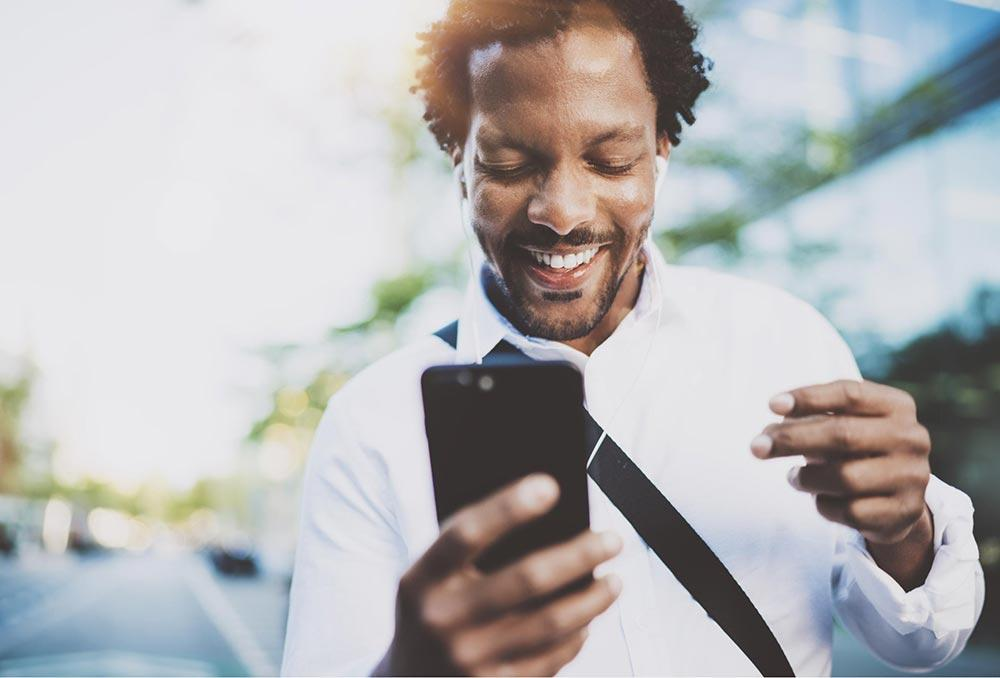 Man looking into his phone and smiling